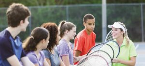 Multi-ethnic group of teenagers (14 to 17 years) at tennis clinic with instructor (30s). Main focus on boy in red shirt (14 years, mixed race African American / Caucasian).